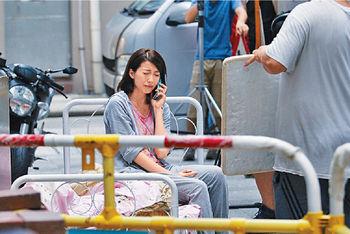 她喺後巷,扮傾電話獨自做戲。